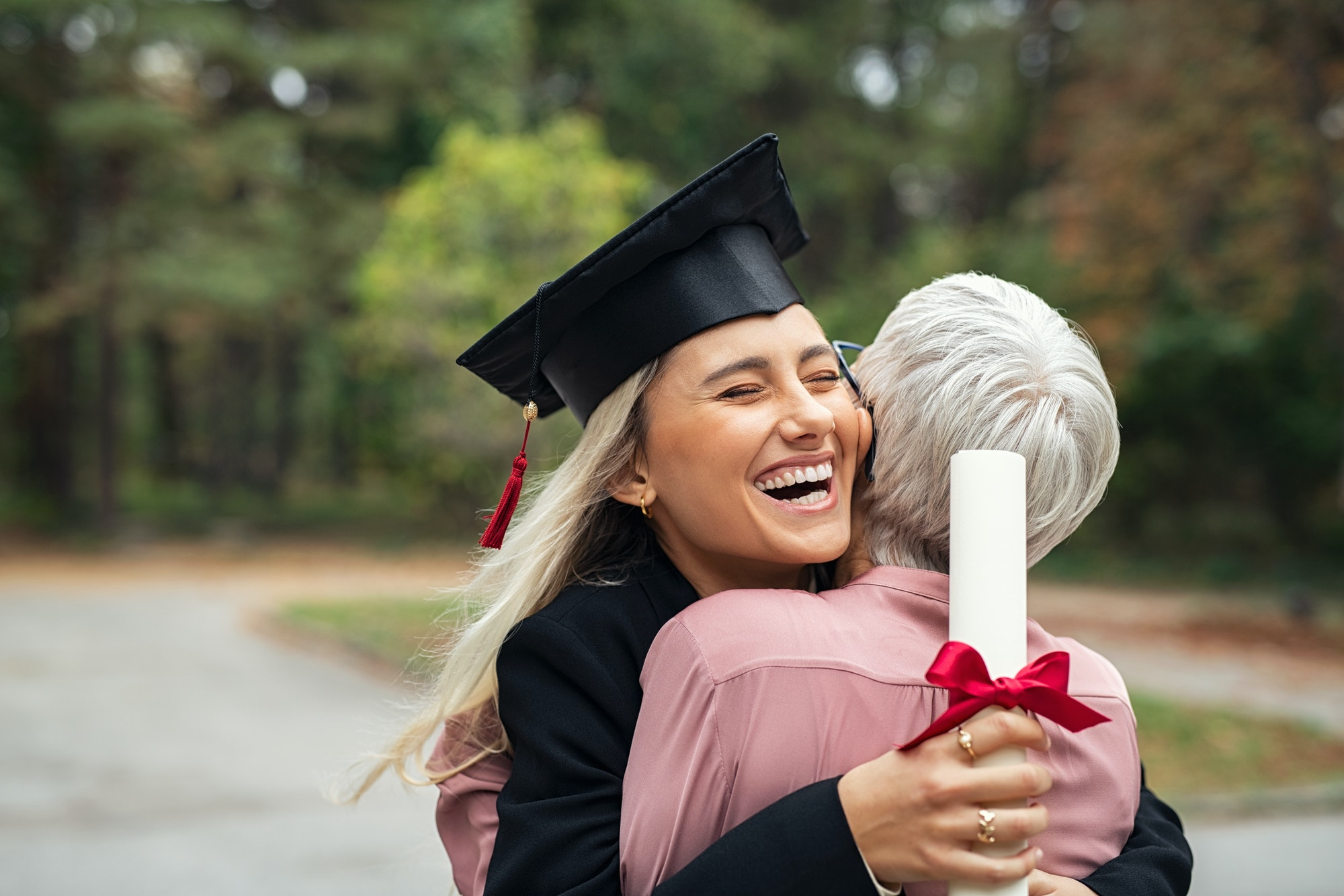 Graduate girl hugging mother